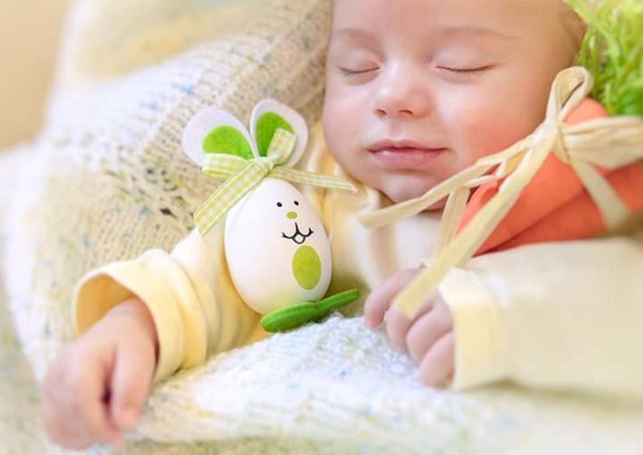 Lächelndes, schlafendes Baby mit Tränchen im Auge
