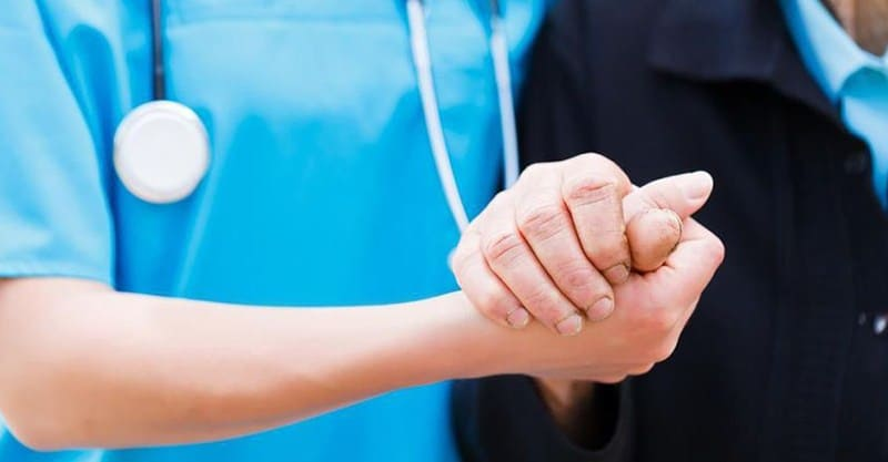 Nurse Holding Hand Of Senior Citizen