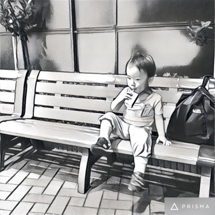 ベンチでジュースを飲む息子。