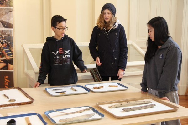 Students looking at Inuit tools such as snow goggles and crampons for the feet