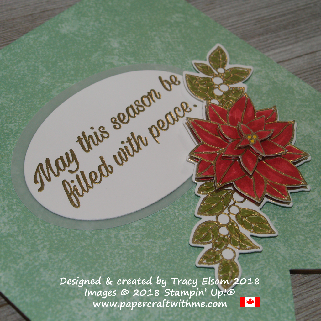 Close up of layered poinsettia image and embossed sentiment on a wooden