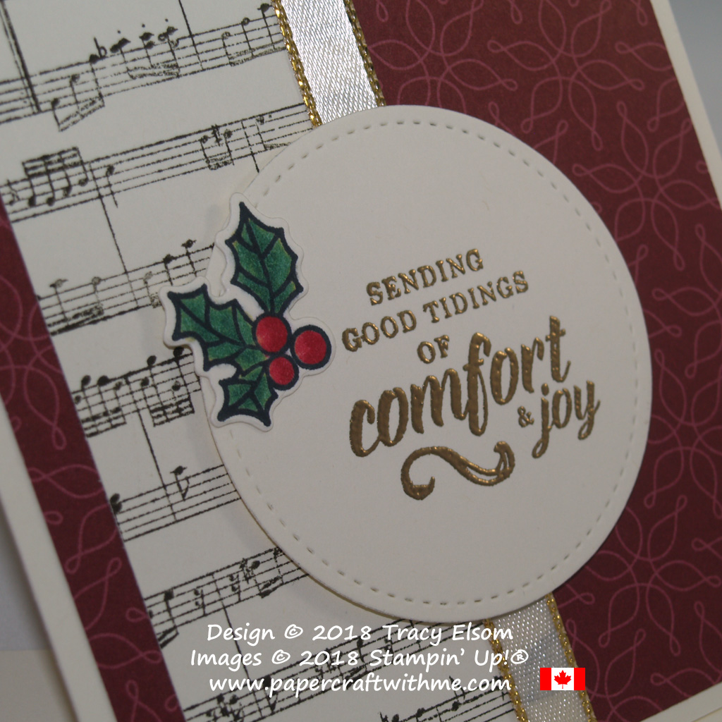 Close up of embossed 'comfort & joy' sentiment from the Timeless Tidings Stamp Set, with holly embellishment and music background created using the Peaceful Poinsettia and Sheet Music Stamp Sets, all from Stampin' Up!