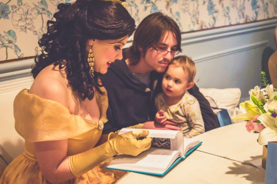 A toddler girl seated with her dad at the table looks on as Princess Belle chooses a story to read at The French Confection Co.