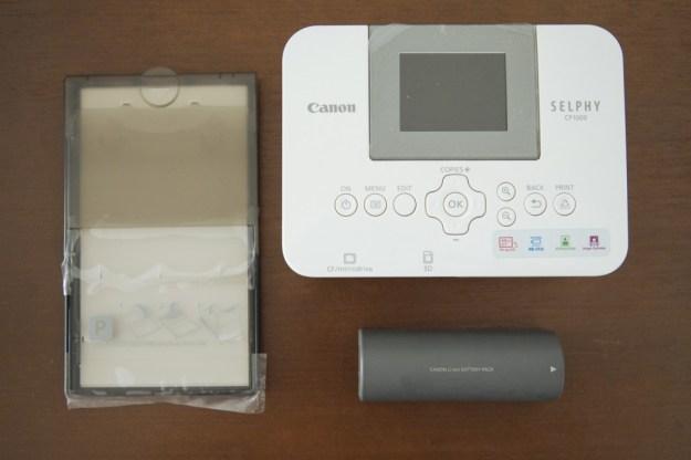Em sentido horário: a impressora Selphy CP1000, com a bateria opcional NP-CP2L e a bandeja PCP-CP400 (cartão postal / 10x15cm)