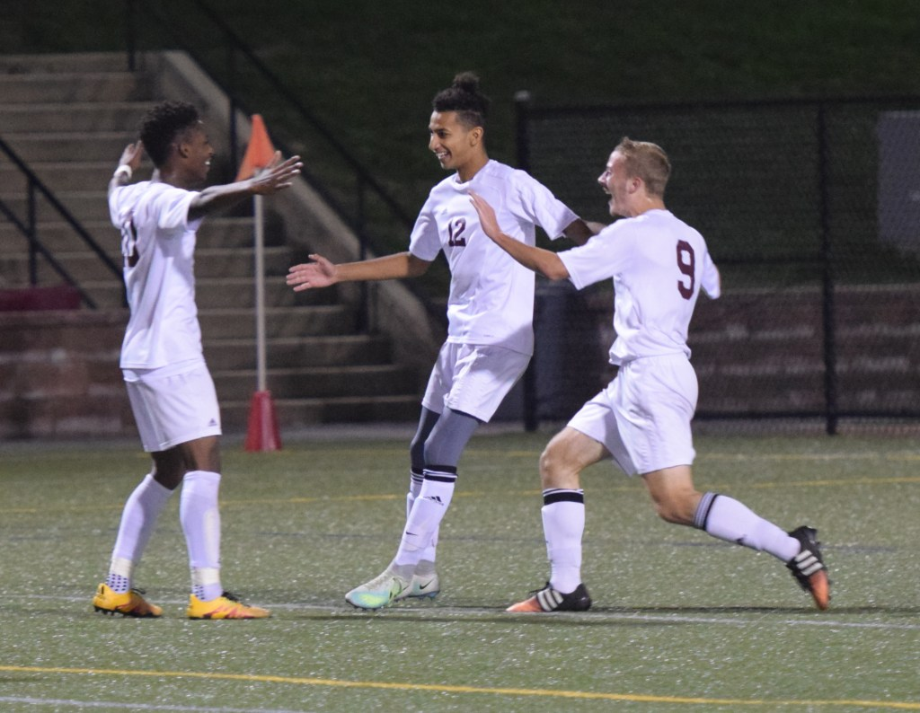 Pottsgrove's Kevin Benitez, center, celebrates with Germann Larmond, left, and Nate Yuchimiuk, who had the assist, on the Falcons' opening goal Tuesday against Owen J. Roberts. (Austin Hertzog - Digital First Media)