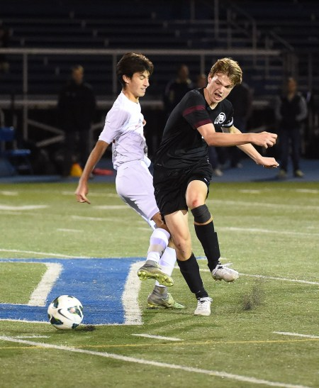 Radnor's Jack Miller, right, takes the ball away from Holy Ghost's Ryan Danastorg and starts a break that would result in a winning goal in overtime by Andrew Boujoukos, lifting Radnor to a District 1 championship Saturday night at Great Valley High School. (Digital First Media/Pete Bannan)