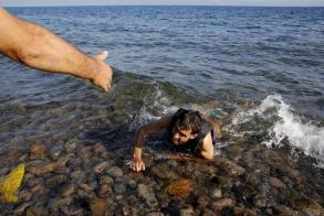Yannis Behrakis - 17 september 2015 : Een lokale man helpt een Syrische vluchteling, die van boord sprong van een rubberboot, als hij uitgeput aankomt bij een strand op Lesbos