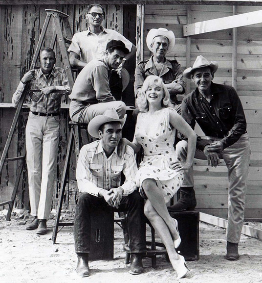 "Arthur Miller and John Huston pose with the cast of ""The Misfits"""