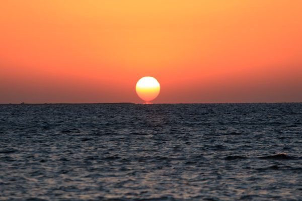 Sun rises up above the sea with calm water and orange sky