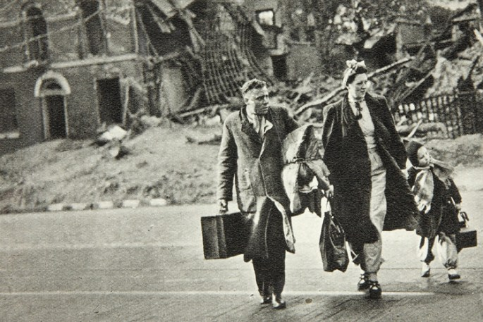 A man and wife cross a road with their young child. A shell of a bombed out house is visible in the background and the people carry one bag each and the man has a roll of clothes under his arm.