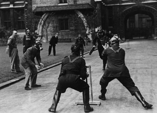 Two teams of men, several wearing gas masks, play cricket in the street.
