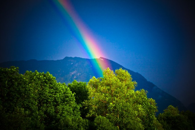 Rainbow vista over a treetop mountain region - the range of colours in the image is the key visual