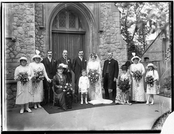 1920s wedding photo showing the bride and groom surrounded by immediate family outside a church