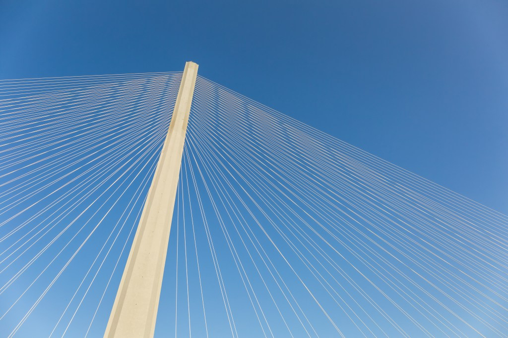 modern bridge tower with stay cables and blue sky, cable-stayed bridge background
