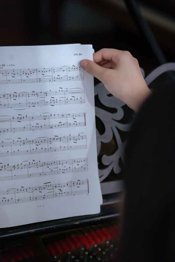 anonymous woman turning page of music book near piano