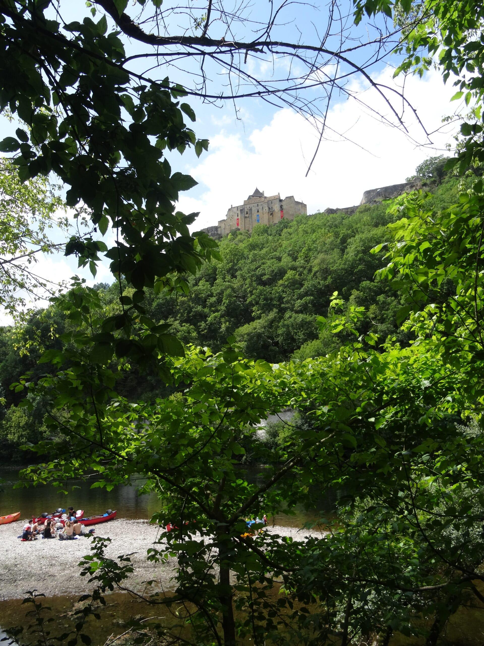 Vue sur le château de Castelnaud à travers la végétation sur les rives de la Dordogne