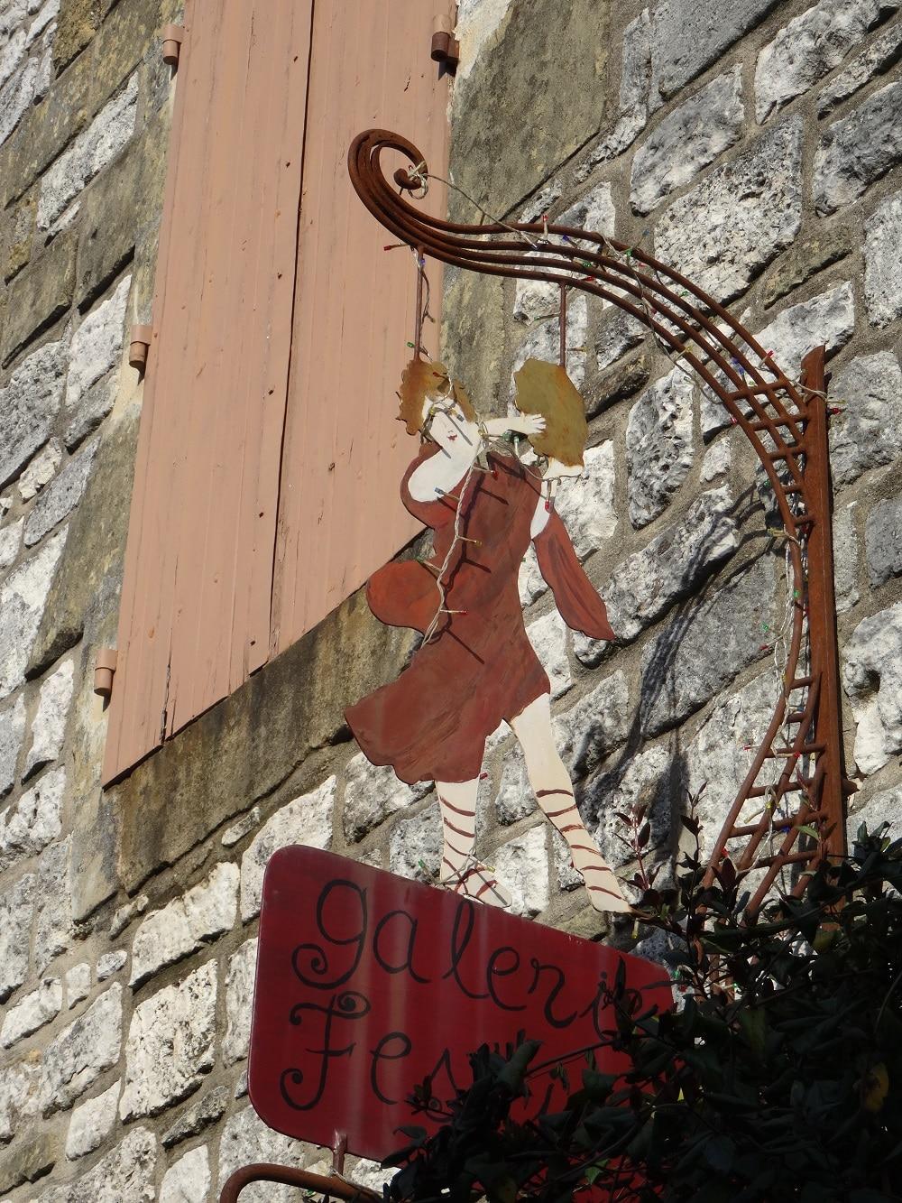 Une enseigne sur les façades de Monpazier