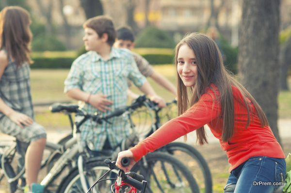 Teenage girl having fun on bicycles with her friends in the park
