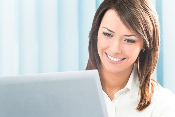 Happy smiling businesswoman with computer at office