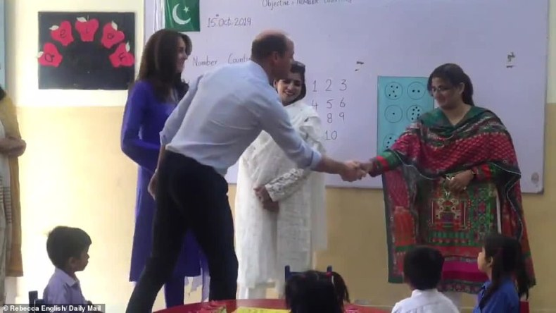 A warm welcome: William shakes the hand of one of the teachers at the Islamabad Model College for Girls in the capital