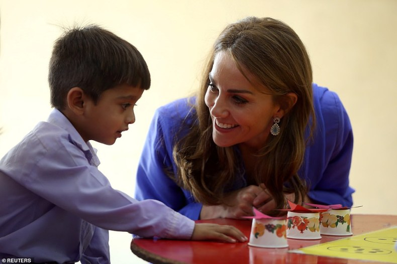 The Duchess of Cambridge interacts with a student at a school on a visit to Islamabad today