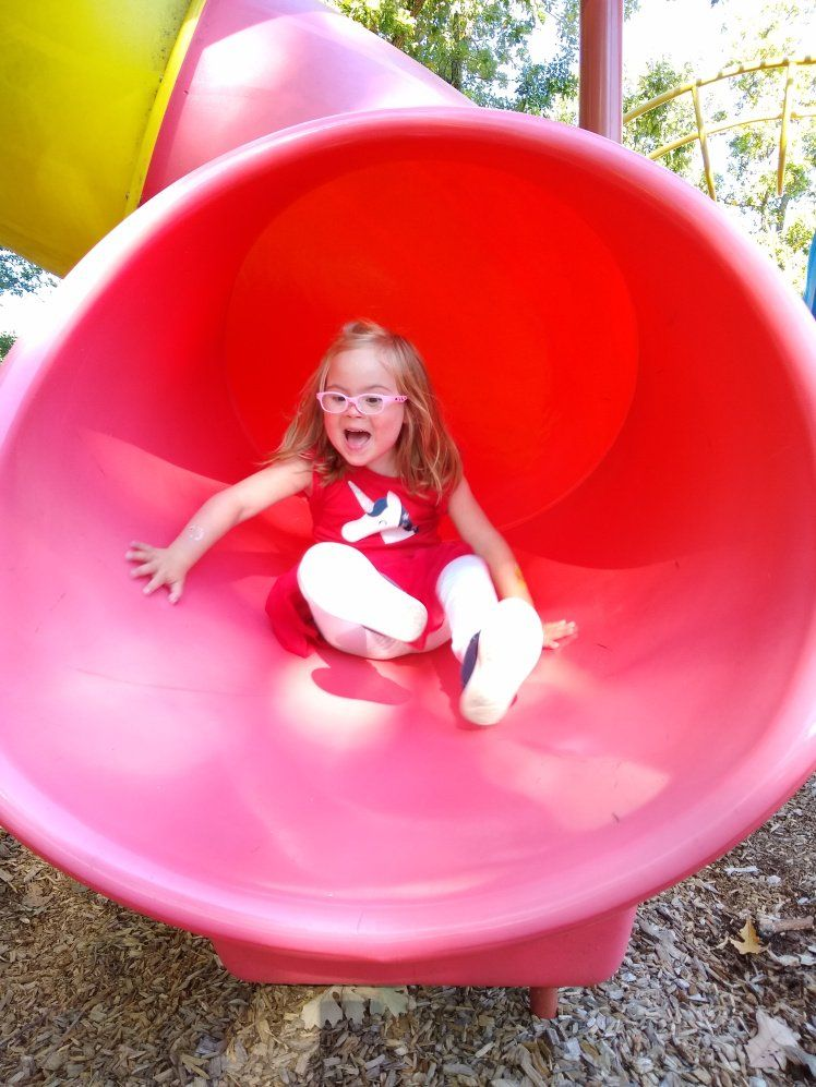 Willow playing in a pink tube slide.
