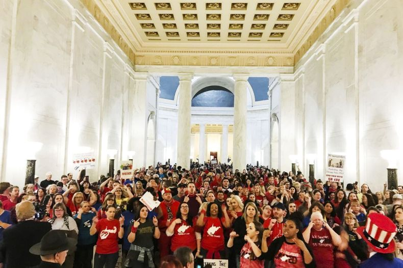 Teachers celebrate after West Virginia Gov. Jim Justice announced they reached a tentative deal to end a statewide teachers' strike on March 6, 2018.
