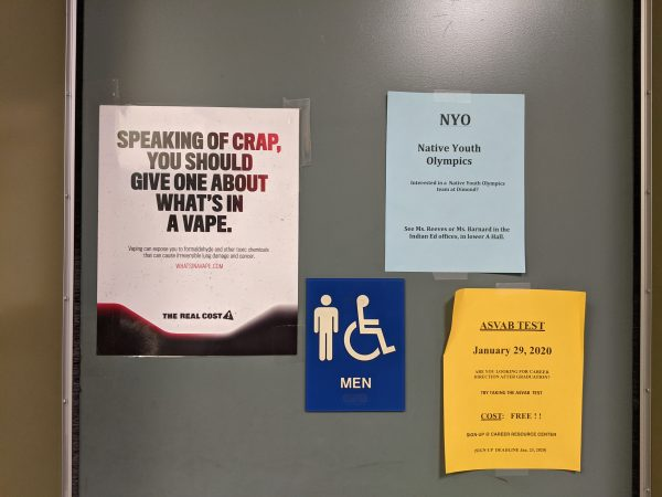 A picture of a men's bathroom door that has some posters including a public awareness poster about toxic chemicals in vape pens
