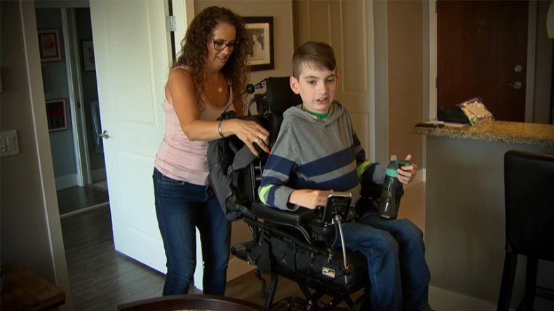 Miles's mom adjusts his wheelchair.