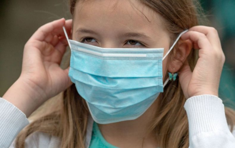 A primary school-aged girl puts on a mask before entering a school in Frankfurt. (Getty Images)