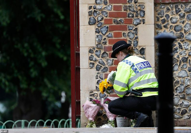 A police officer places the floral tributes near to the scene of the attack last night, which also left three people seriously injured