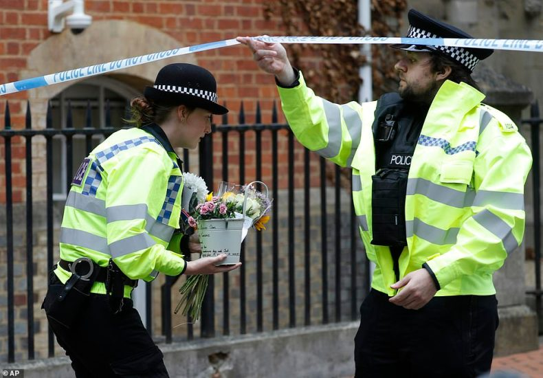 Police officers collect floral tributes left at the Abbey gateway of Forbury Gardens in Reading after three people died last night in a multiple stabbing attack