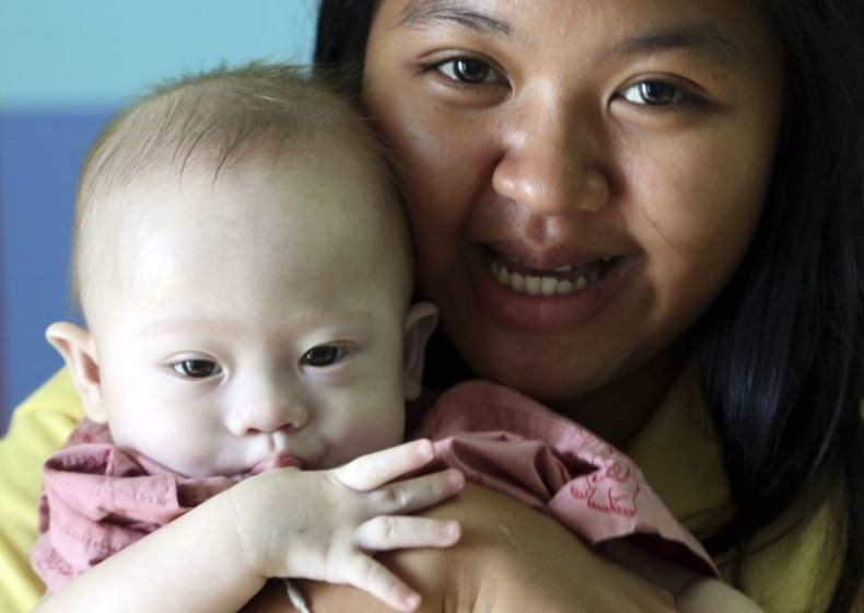 Thai surrogate mother Pattaramon Chanbua, a 21-year-old food vendor, poses with Gammy at nine months. Source: AAP