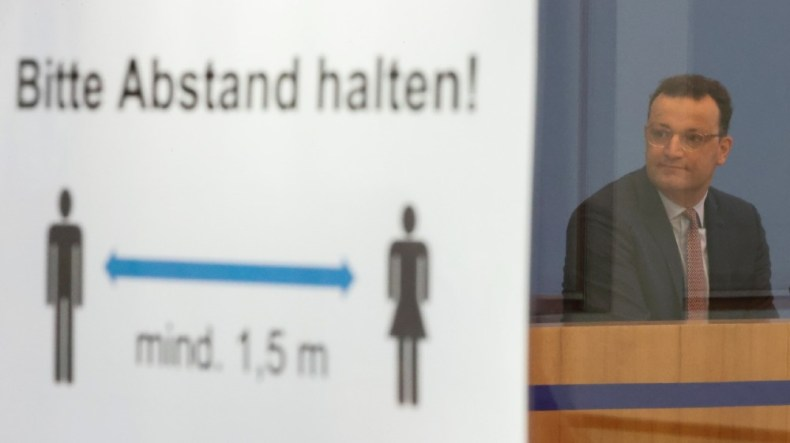 German Health Minister Jens Spahn is seen next to a social distancing sign reading