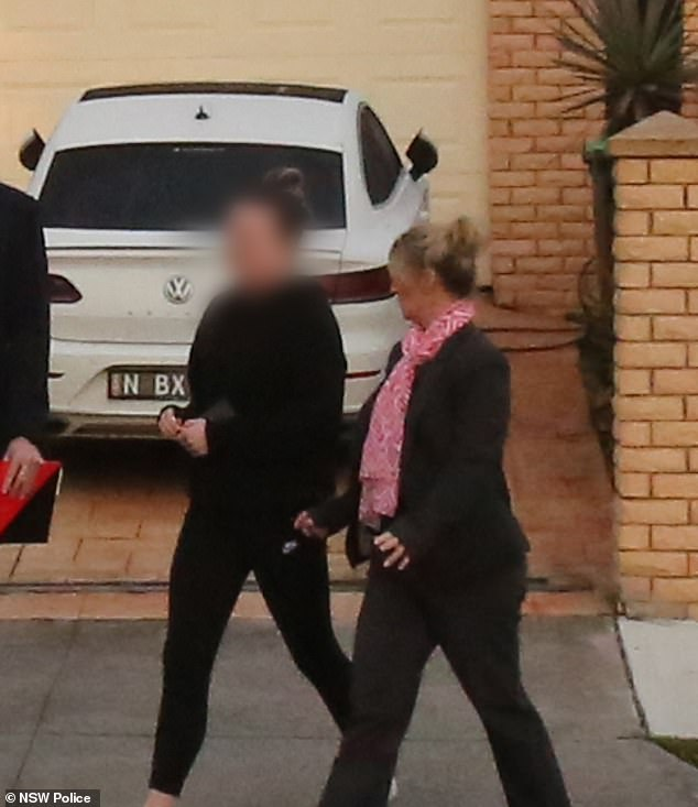 Officers were filmed escorting the woman out of the premises before seizing a car and electronic devices