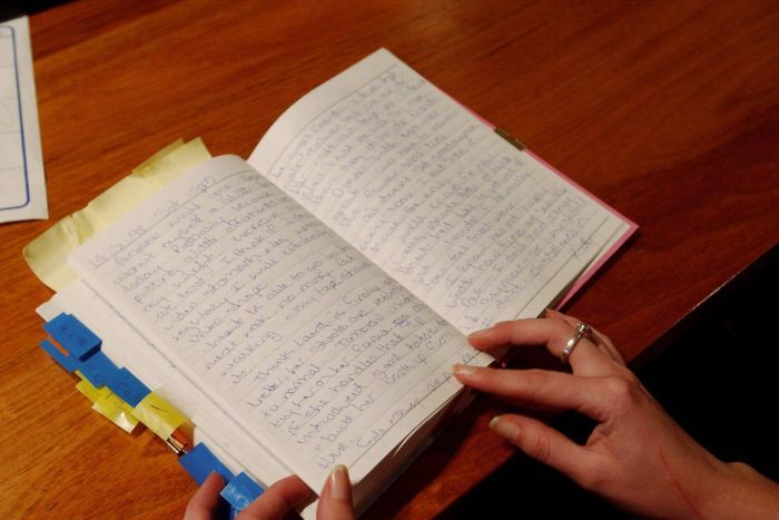 A woman's hands on an open diary