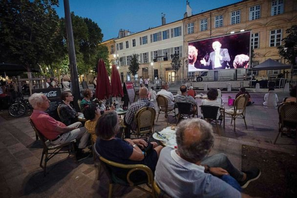 PHOTO: People look at a video projection of a concert, recorded by the Baltasar Neumann Orchestra at the Cours Mirabeau plaza in Aix-en-Provence on July 21, 2020. (Clement Mahoudeau/AFP via Getty Images)