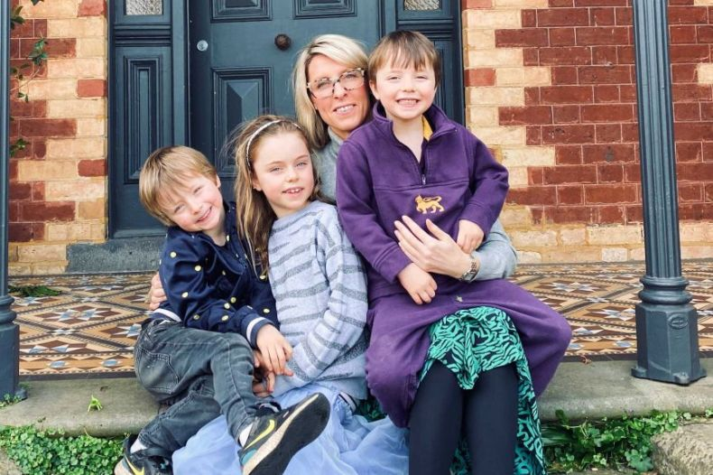 A mother sits on a doorstep with her three children sitting with her.