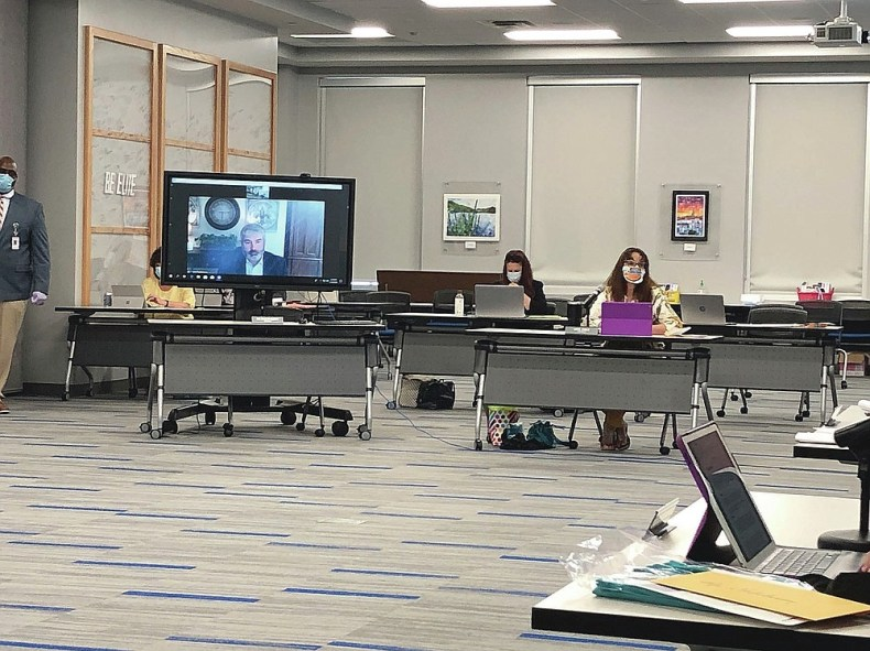 Rock Hill School Board member Windy Cole, right and Brett Faulkenberry, left, attending remotely, listen to a question during a board meeting in Rock Hill, South Carolina, on Monday, Aug. 10, 2020. Like school boards across the nation, Rock Hill's board has had to answer the simple question when do children return to school with no easy or guaranteed safe answer. (AP Photo / Jeffrey Collins)