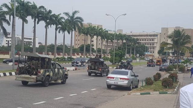 Armed security inside vans during Protesters wey dey carry sign boards
