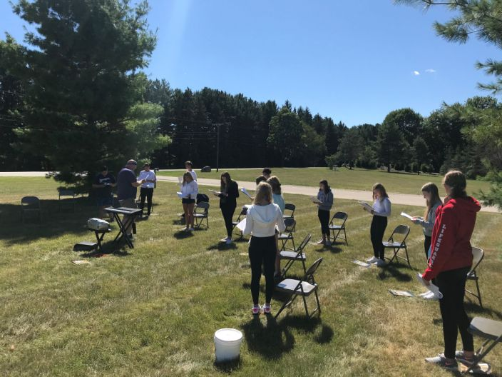 Lake Country School music teacher James Bakken (near keyboard) and his eighth grade choir class get some singing practice in outside. They have their masks off due to being outside and having six feet of separation between them.