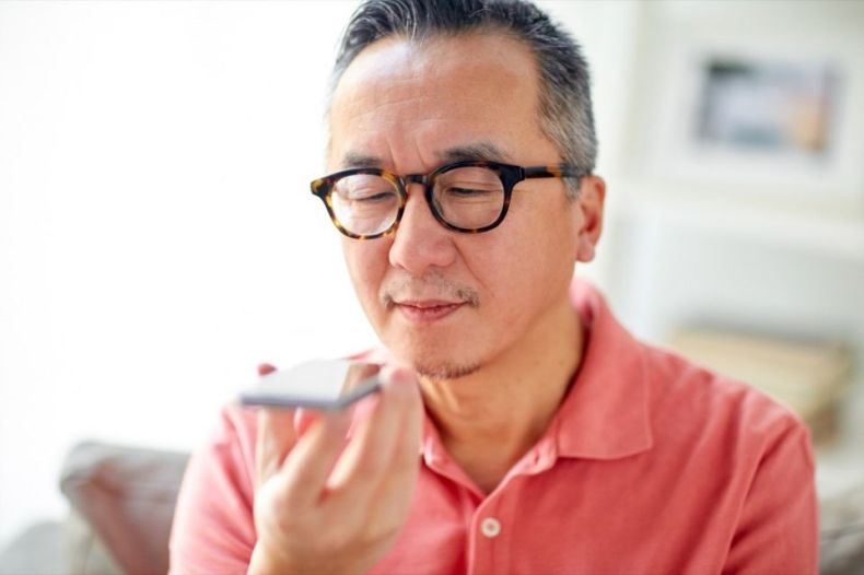 happy man using voice command recorder on smartphone at home