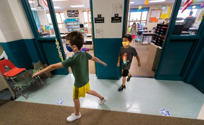 Second grade students at Lake Country School in Hartland place their arms out to maintain proper social distancing while heading outside for recess on Sept. 4, 2020. The school put in place measures designed to prevent the spread of the coronavirus.
