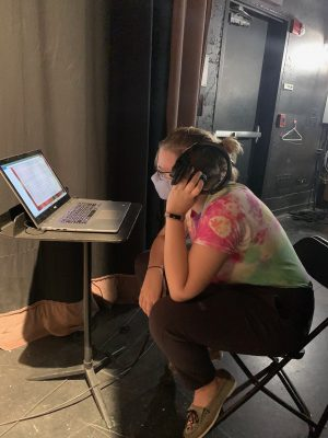 Lead production assistant Elizabeth Koetz listens to studio recordings to monitor for unwanted room noise