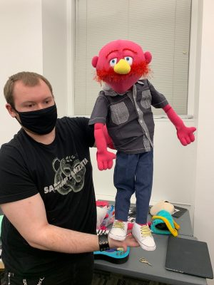 Lead puppet designer shows off his puppet for Pork Tornadoes' keyboardist, Jerry Lorenson.
