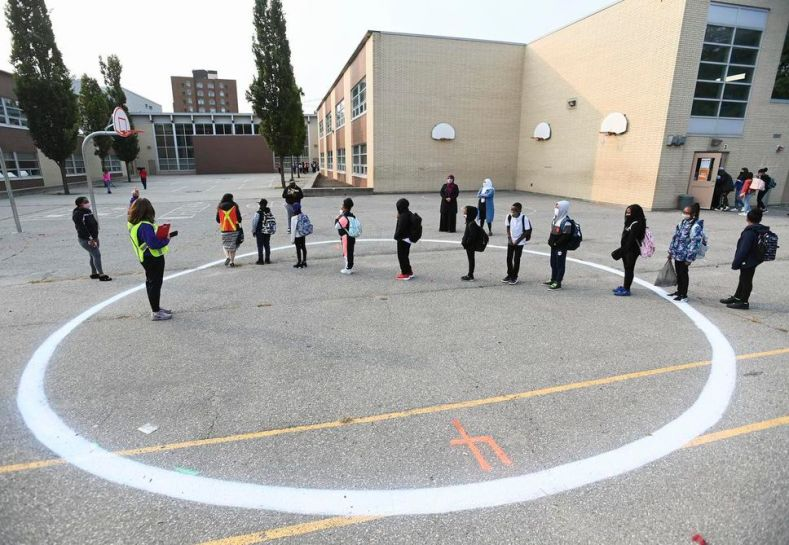 Children wait in a physical distancing circle at Portage Trail Community School, part of the TDSB, last month.