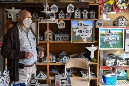 Edgar Fischel, who will turn 93 on Dec. 2, stands in his garage amid his creations on Thursday, Nov. 12, 2020. Fischel's hobby for more than 20 years has been building homes, not for people, but for birds using license plates and recycled materials. Fischel, a retired educator, has expanded his offerings to include framed outlines of Texas, trash cans and replicas of the historic missions.