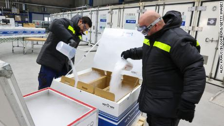 Employees fill a clinical and pharmaceutical product shipping box with dry ice at the Va-Q-Tec AG factory in Wurzburg, Germany, on November 18.