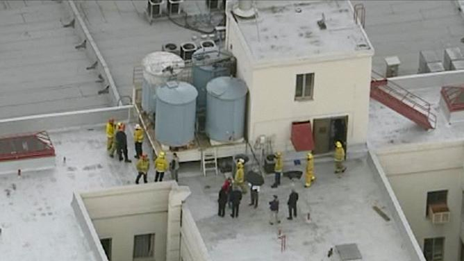 Firefighters and police officers on the Cecil hotel roof in Crime Scene: The Vanishing at the Cecil Hotel.