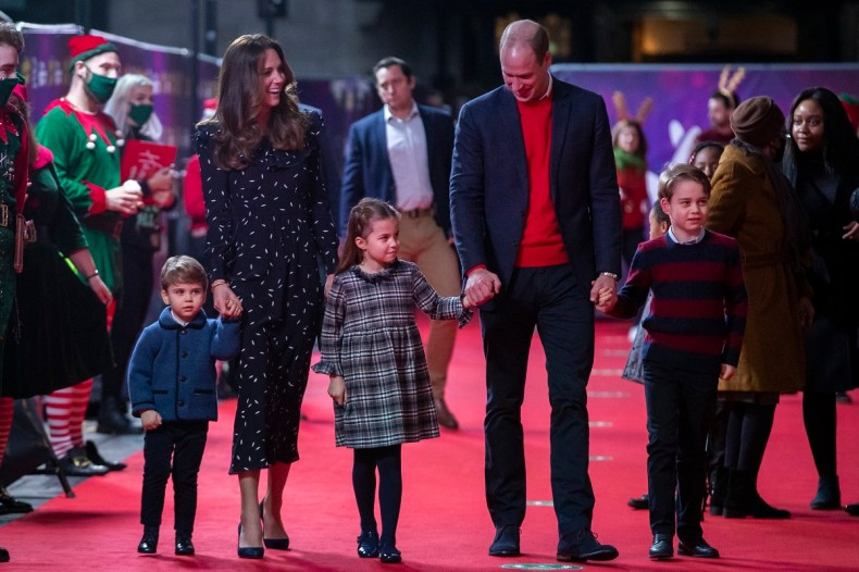 Prince William and Kate Middleton hold hands with their children as they walk the red carpet at a performance in London